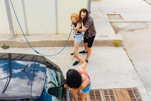 Vrienden bespattend water op vrouw die zich dichtbij auto bevindt Gratis Foto