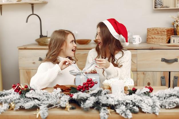 Vrienden brachten tijd thuis door. twee meisjes drinken thee. vrouw in de hoed van een kerstman. Gratis Foto