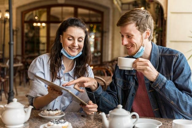 Vrienden chatten in het restaurant terwijl ze medische maskers op hun kin hebben Gratis Foto