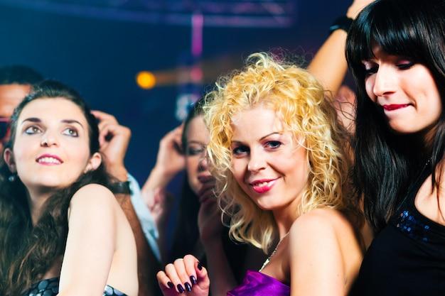 Vrienden dansen in club of disco Premium Foto