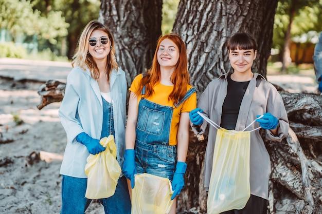Vrienden die afval uit het park oppakken. ze verzamelen het afval in een vuilniszak Gratis Foto