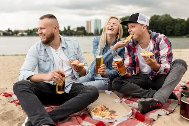 Vrienden die bier drinken en pizza eten Premium Foto