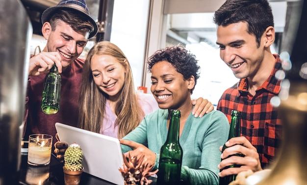 Vrienden die bier drinken en pret met tablet hebben Premium Foto