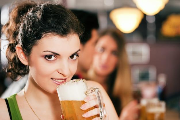 Vrienden die bier in bar drinken Premium Foto