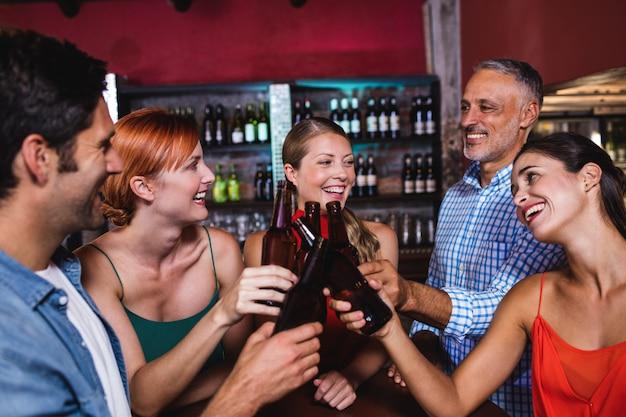 Vrienden die bierfles in nachtclub roosteren Premium Foto