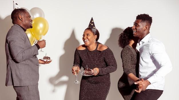 Vrienden die cake eten en dansen Gratis Foto