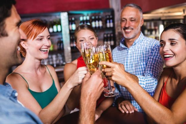Vrienden die champagneglas in nachtclub roosteren Premium Foto