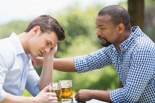 Vrienden die een gesprek hebben terwijl het hebben van bier Premium Foto