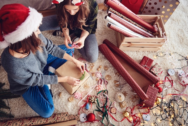 Vrienden die een kerstcadeau versieren Gratis Foto