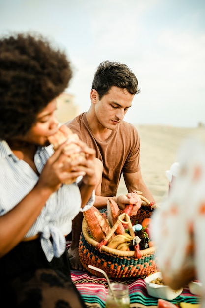 Vrienden die een picknick van het de zomerstrand hebben Premium Foto
