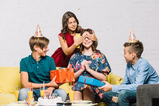 Vrienden die giften geven aan het feestvarken door haar ogen op feest te dekken Gratis Foto