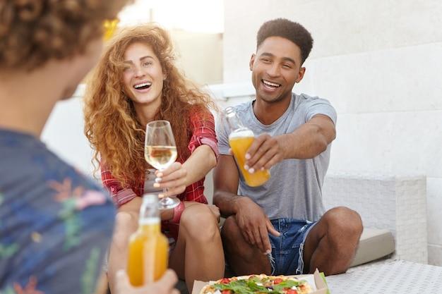 Vrienden die hun glazen rammelen met wijn en bier Gratis Foto