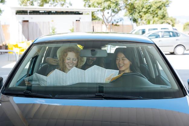 Vrienden die kaart onderzoeken terwijl het zitten in auto bij benzinepost Gratis Foto