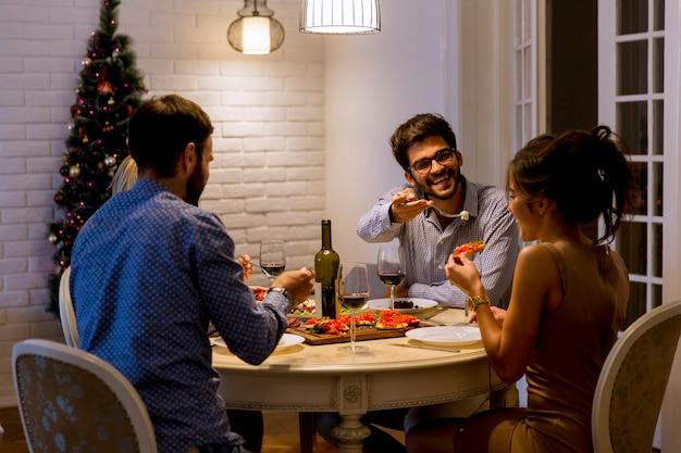 Vrienden die kerstmis of nieuwjaarvooravond thuis vieren Premium Foto