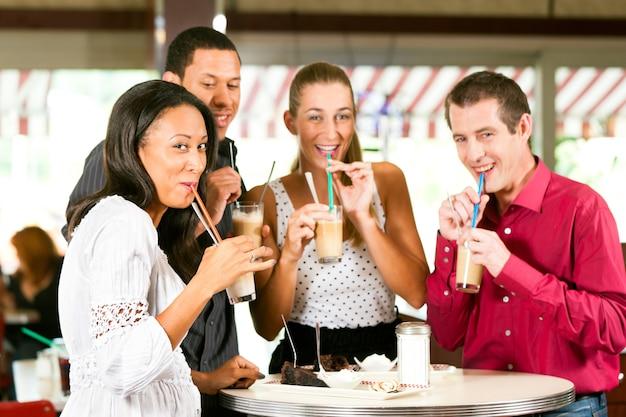 Vrienden die melkkoffie drinken en cake eten Premium Foto