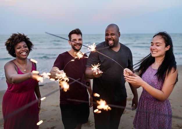 Vrienden die met sterretjes bij het strand vieren Premium Foto