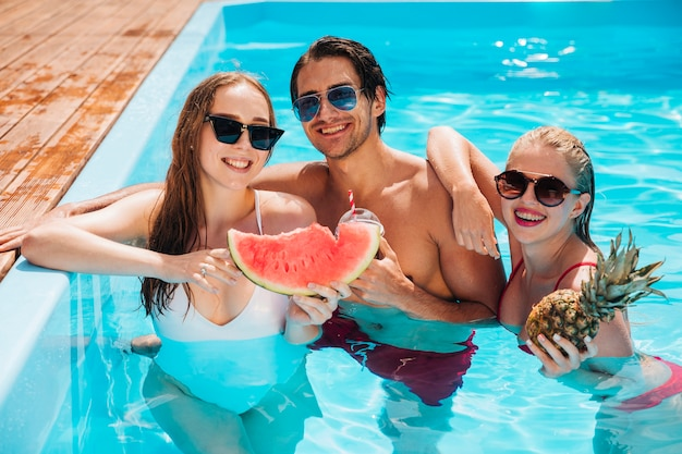 Vrienden die met watermeloen en ananas stellen Gratis Foto