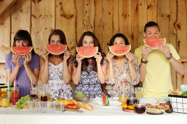 Vrienden die met watermeloenplakken stellen Gratis Foto