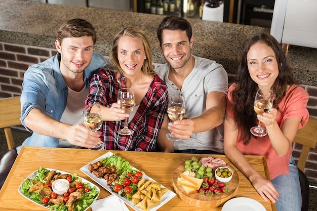 Vrienden die met witte wijn roosteren Premium Foto