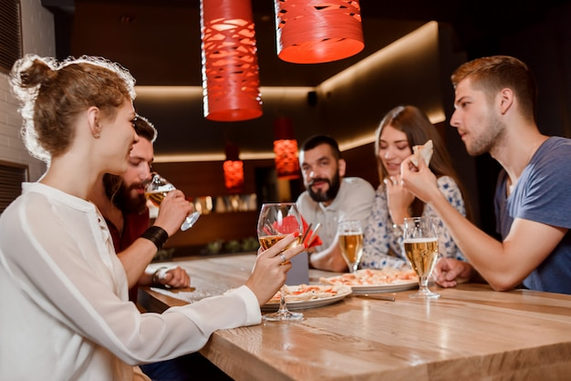 Vrienden die pizza eten en bier in pizzeria drinken. Premium Foto