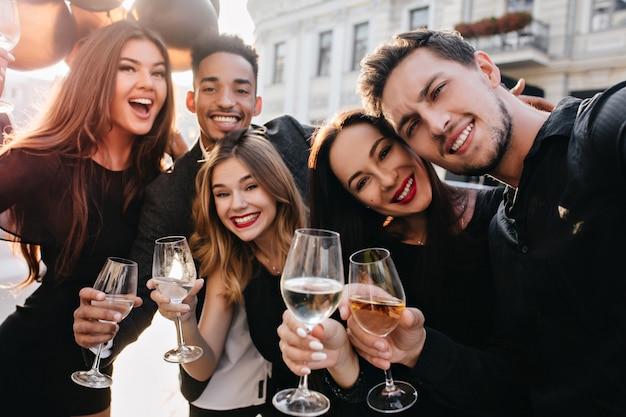 Vrienden die plezier hebben en buiten champagne drinken Gratis Foto