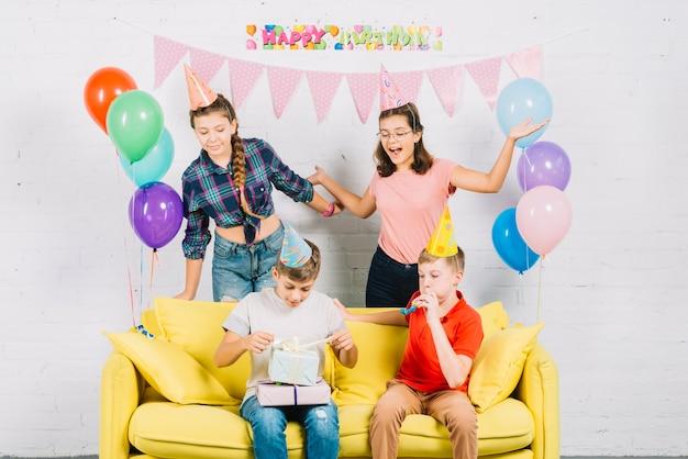 Vrienden die pret hebben terwijl jongenszitting op bank die verjaardagsgiften thuis opwikkelen Gratis Foto