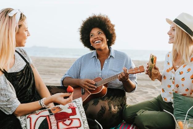 Vrienden die samen op een strandpicknick zingen Premium Foto