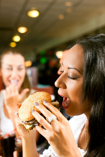 Vrienden die snel voedsel in een restaurant eten Premium Foto