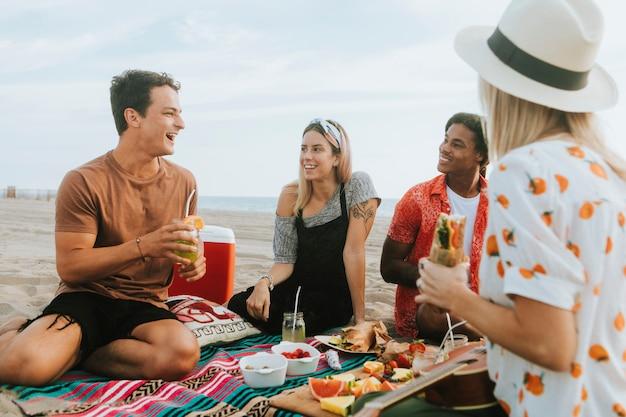 Vrienden die voedsel eten bij een strandpicknick Premium Foto