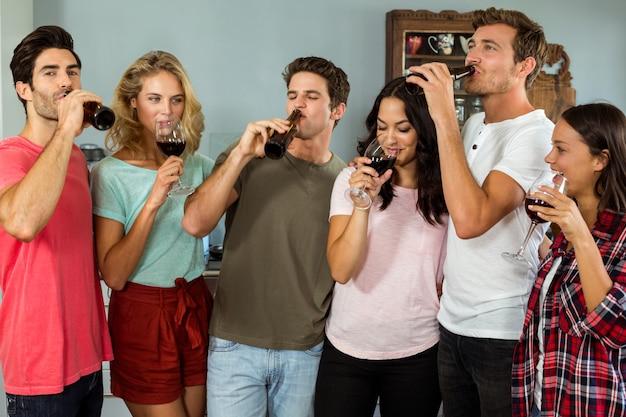 Vrienden die wijn en bier thuis drinken Premium Foto