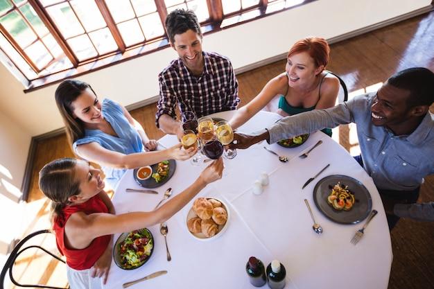 Vrienden die wijnglas roosteren bij lijst in restaurant Premium Foto