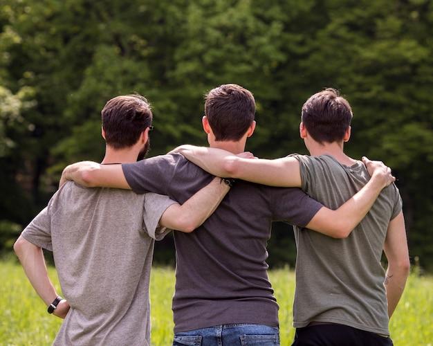 Vrienden die zich op open plek met handen op elkaar schouders bevinden Gratis Foto