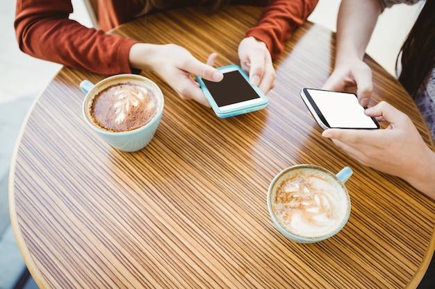 Vrienden gebruikend smartphone en hebbend koffie in een koffiewinkel Premium Foto
