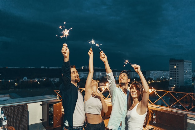 Vrienden genieten van een rooftop party Gratis Foto