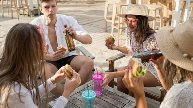 Vrienden genieten van hamburgers buiten met drankjes Gratis Foto