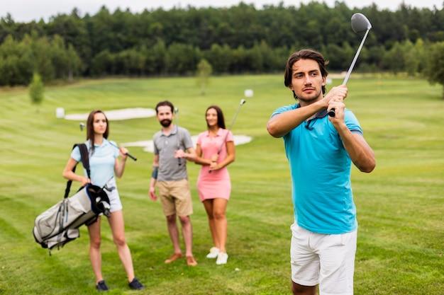 Vrienden golfen op veld Gratis Foto