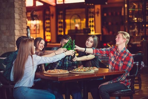Vrienden hebben een drankje in een bar, ze zitten aan een houten tafel met bier en pizza. Premium Foto