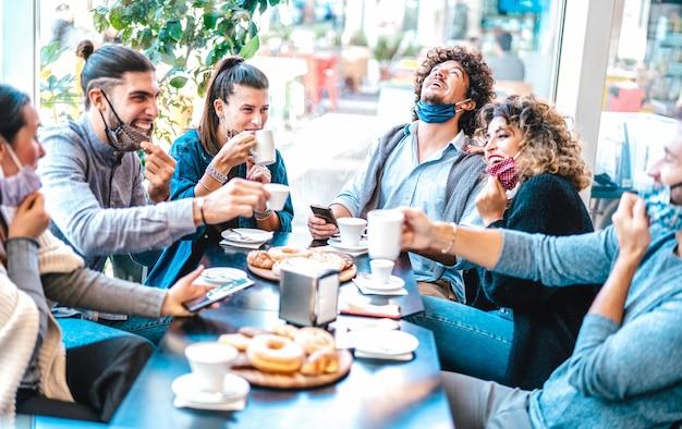 Vrienden hebben plezier bij het drinken en eten bij koffiehuis Premium Foto