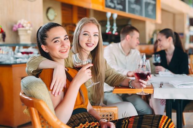 Vrienden hebben plezier in het drinken van wijn, praten en lachen in het restaurant. Premium Foto