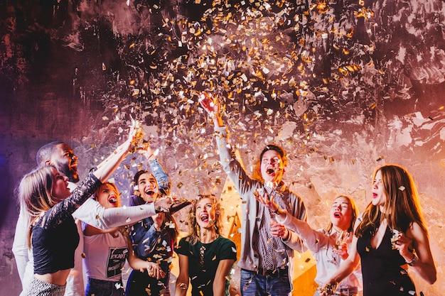 Vrienden hebben plezier in het vallen van confetti Gratis Foto