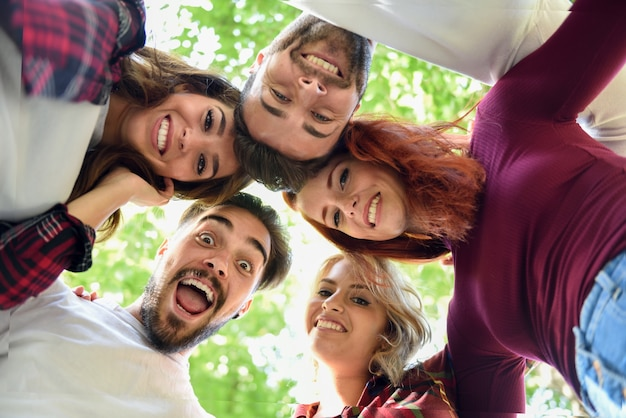 Vrienden in cirkel met de koppen bij elkaar glimlachen Gratis Foto