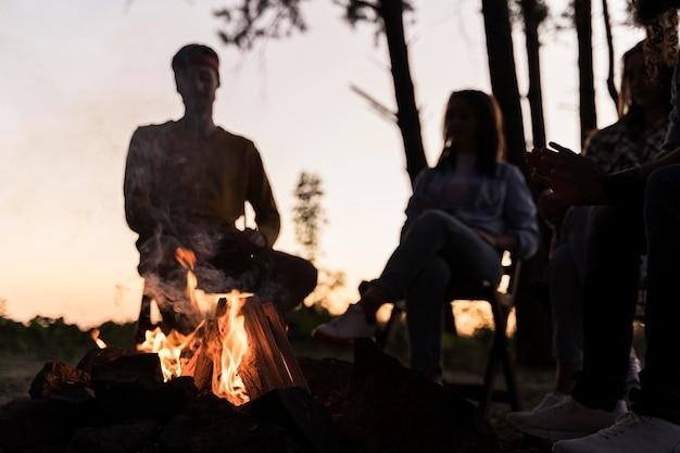 Vrienden in de schemering verzamelen zich rond een vuur Gratis Foto