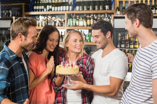 Vrienden in een cirkel die een cake houdt Premium Foto