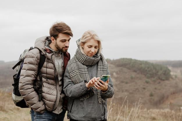 Vrienden kijken naar telefoon buitenshuis Gratis Foto