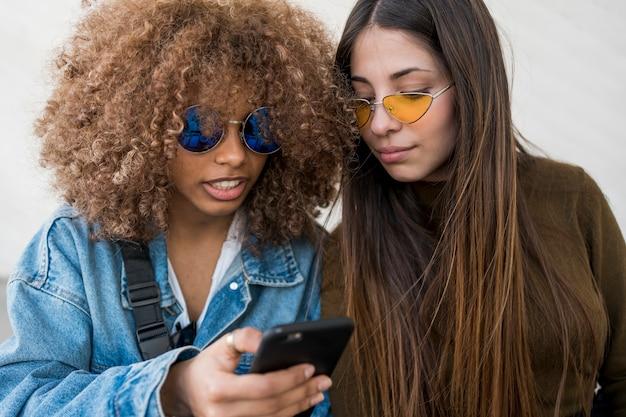 Vrienden kijken naar telefoon Gratis Foto