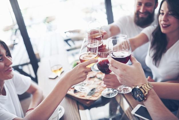 Vrienden kwamen aan tafel bij elkaar met heerlijk eten met glazen rode wijn om een speciale gelegenheid te vieren Premium Foto