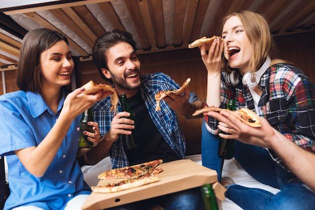 Vrienden lachen, houden pizzaplakken vast en eten. Premium Foto
