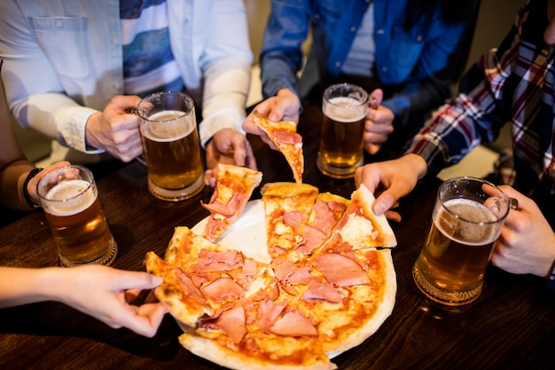 Vrienden met bierpul en pizza in de bar Premium Foto