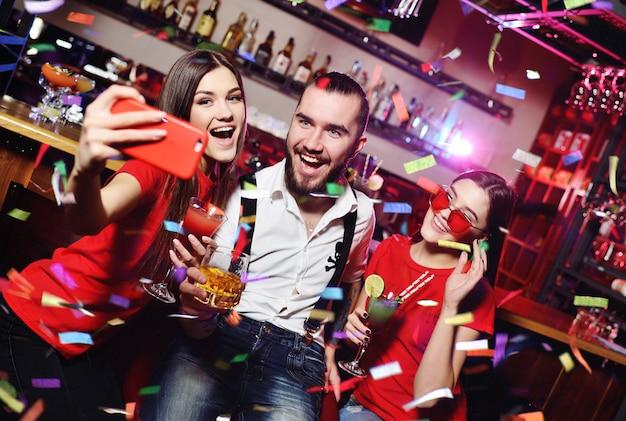 Vrienden met cocktails maken selfie op feestje Premium Foto