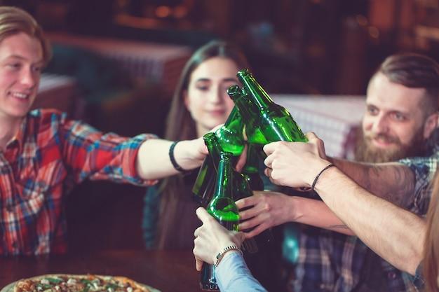 Vrienden met een drankje in een bar, ze zitten aan een houten tafel met bier en pizza. Premium Foto